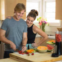 man and woman couple cutting up watermelon and cantaloupe for a smoothie