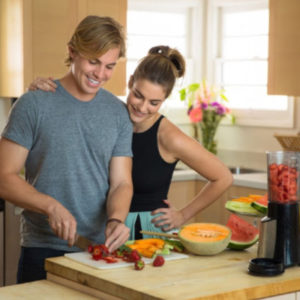 man and woman couple cutting up watermelon and cantaloupe for a smoothie following tips for healthy eating
