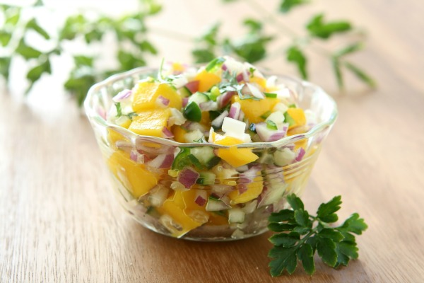 mango salsa in bowl with cilantro leaves