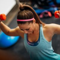 women at gym with free weights following a weight lifting routine
