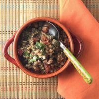 lentil salad with tomato feta and herbs in an orange bowl