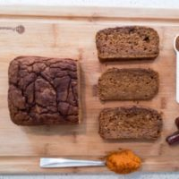healthy pumpkin bread loaf with slices on a cutting board