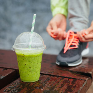 Green post-exercise protein shake and woman tying shoe