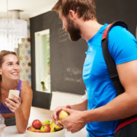 man and woman in kitchen with fruit bowl deciding what to eat before working out - melissashealthyliving.com