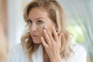 Woman looking in the mirror for fine lines after taking collagen supplements