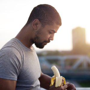 black man holding a banana before a run for nutrition for runners